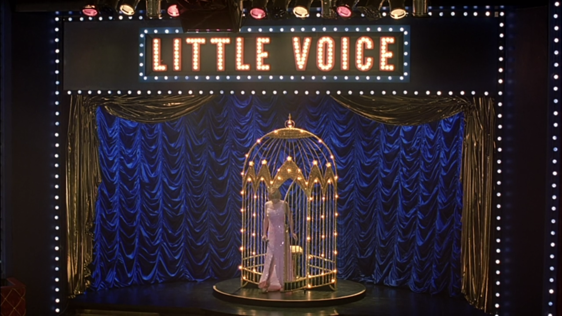 "A woman onstage emerges from a golden cage, the words ""Little Voice"" appearing in lights above her."